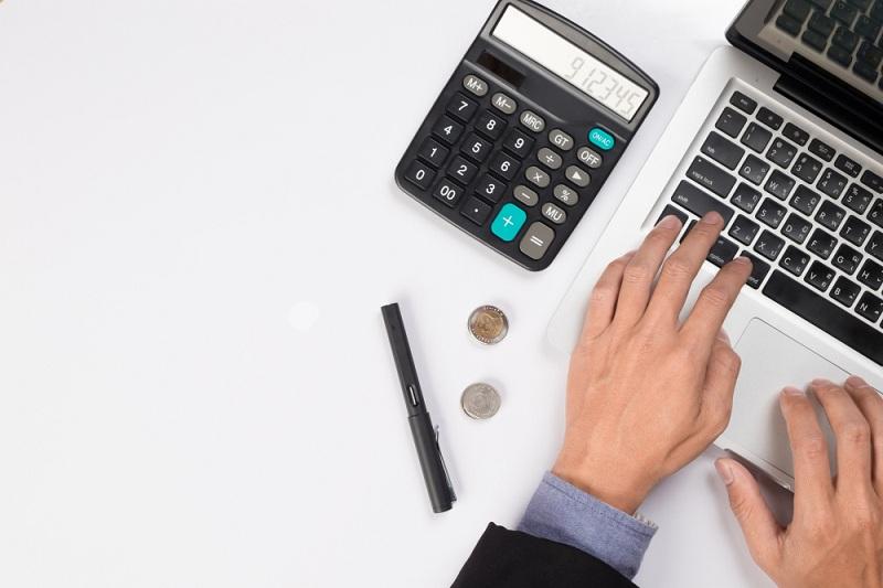 como abrir uma empresa de educação financeira - mãos usando computador e calculadora