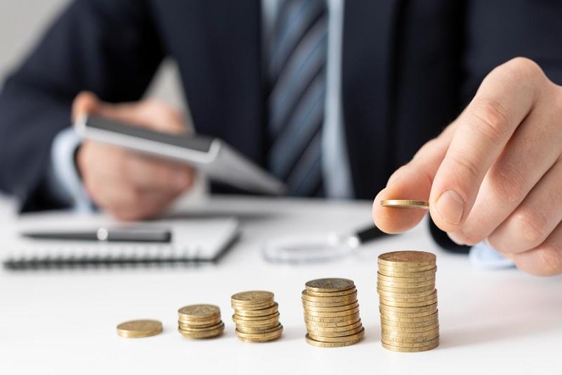 o que é holding e como gerenciar patrimônio. Homem contando moeda.